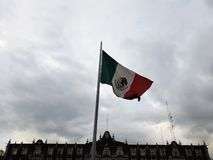 Flag of the Mexican Republic waving aloft with the wind. National emblem and symbol of Mexico, patrotism and nationalism royalty free stock images