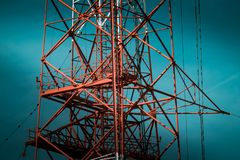 National Energy Grid system. Power pylons connecting the country. Red steel structures on deep blue sky stock photos