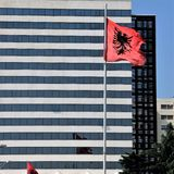 The national flag of Albania against the backdrop of a super-modern hotel in the capital Tirana. stock photography