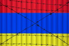 National flag of Armenia on fence. Barbed wire in the foreground symbolizes entry ban or prohibition for crossing border of countr royalty free stock photography
