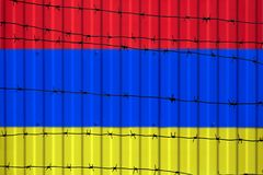 National flag of Armenia on fence. Barbed wire in the foreground symbolizes entry ban or prohibition for crossing border of countr. Y Stock Images