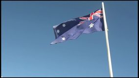 The National flag of Australia. Against blue sky stock footage