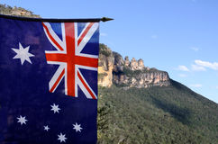 The National flag of Australia flay beside the Three Sisters Blu Stock Images