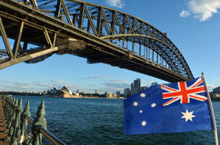 The National flag of Australia flay under Sydney Harbour Bridge. And the Opera House in Sydney, Australia Stock Image