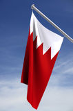 National flag of Bahrain. A view of the red and white national flag of the country of Bahrain on a short, white flagpole against a sky setting. Clipping path stock photography