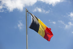 National flag of Belgium on a flagpole. In front of blue sky Stock Images