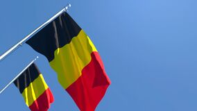 The national flag of Belgium is flying in the wind against a blue sky