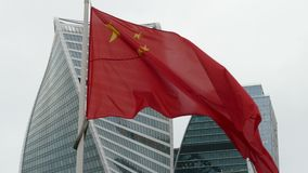 The national flag of China. Against the backdrop of skyscrapers stock video