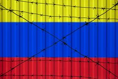 National flag of Colombia on fence. Barbed wire in the foreground symbolizes entry ban or prohibition for crossing border of count. Ry Royalty Free Stock Photos
