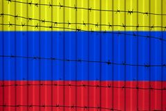National flag of Colombia on fence. Barbed wire in the foreground symbolizes entry ban or prohibition for crossing border of count. Ry Stock Photos