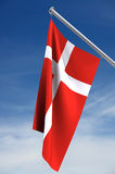 National flag of Denmark. A close up view of the red and white national flag of Denmark flying from a flag pole against a blue sky with white clouds. Clipping vector illustration