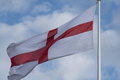 English flag associated with nationalism and BNP. National flag of England St Georges flag blowing in the wind with blue sky in background royalty free stock photos
