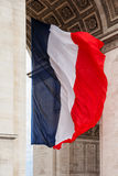 National flag of France with detail of triumphal arch, Paris, Fr. National flag of France with detail of triumphal arch (Arc de triumphe), Paris, France Royalty Free Stock Image