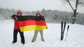National flag of German waving in the wind. With blurred mountains in the background. Two people hold the flags in a blizzard and a strong wind stock footage