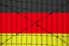 National flag of Germany on fence. Barbed wire in the foreground symbolizes entry ban or prohibition for crossing border of countr. Y Stock Photography