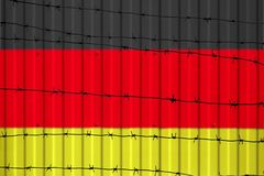 National flag of Germany on fence. Barbed wire in the foreground symbolizes entry ban or prohibition for crossing border of countr. Y Royalty Free Stock Photo