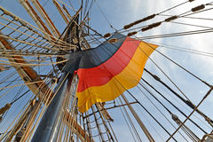 National flag of Germany flutters among ropes of the sailing vessel Stock Image