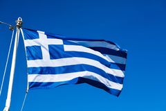National flag of Greece. Big national flag of Greece closeup against the background of the blue sky Stock Image