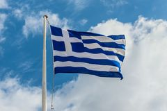 National flag of Greece flying in wind. And blue cloudy sky Royalty Free Stock Photography