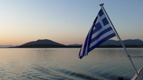 National flag of Greece waving on a ferry traveling from Corfu Island to Igoumenitsa.  stock video footage