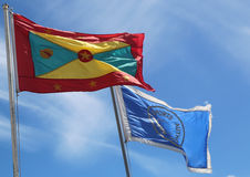 The national flag of Grenada and  Grenada Airports Authority flag at Maurice Bishop International Airport in Grenada. TRUE BLUE, GRENADA - JUNE 13, 2017: The Royalty Free Stock Photos