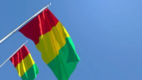 The national flag of Guinea flutters in the wind against a blue sky