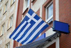 National flag of the Hellenic Republic flutters on a building facade.  Stock Photos