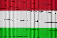 National flag of Hungary on fence. Barbed wire in the foreground symbolizes entry ban or prohibition for crossing border of countr. Y Stock Image