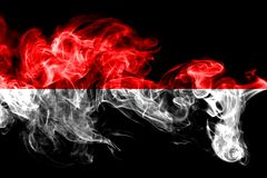 National flag of Indonesia made from colored smoke isolated on black background. Abstract silky wave background. National flag of Indonesia made from colored royalty free stock photography