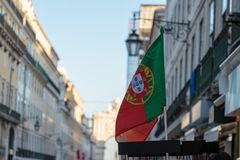 National Flag inside Exhibitor in Lisbon Shop, Portugal. National Flag ine Exhibitor and Rua Augusta Arch in background in Lisbon Shop, Portugal Royalty Free Stock Images