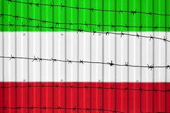 National flag of Iran on fence. Barbed wire in the foreground symbolizes entry ban or prohibition for crossing border of country. National flag of Iran on fence Stock Images