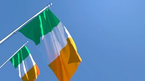 The national flag of Ireland is flying in the wind against a blue sky