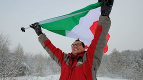 National flag of Italy waving in the wind. With blurred mountains in the background. Man hold the flags in a blizzard and a strong wind stock footage