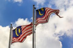 National flag of Malaysia Jalur Gemilang fluttering in the wind against a blue sky with clouds. On a sunny day royalty free stock photo