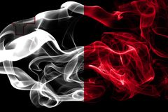 National flag of Malta made from colored smoke isolated on black background. Abstract silky wave background. National flag of Malta made from colored smoke Royalty Free Stock Images