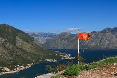 National flag of Montenegro over the Bay of Kotor. National flag of Montenegro at the top of the hill above the Bay of Kotor Royalty Free Stock Photos