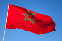 National flag of Morocco on a flagpole. Above clear blue sky stock photo