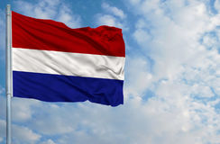 National flag of Netherlands on a flagpole in front of blue sky Royalty Free Stock Photo