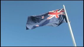 The National flag of New Zealand. Against blue sky stock video footage