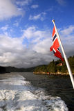 National flag of Norway in Fjord, beautiful nature Royalty Free Stock Images