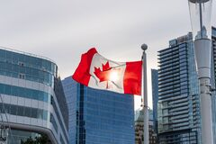Free National Flag Of Canada. Vancouver City Skyscrapers Skyline In The Background With Sunlight. Concept Of Canadian Urban City Life. Stock Images - 213792844