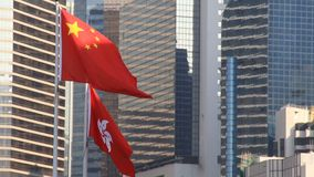 Flags of China and Hong Kong flying in the wind. National flag of People`s Republic of China and flag of Hong Kong waving in the wind over modern building stock video footage