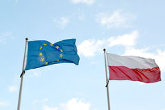 National flag of Poland and flag of the European Union flutter a. Gainst the blue sky Royalty Free Stock Image
