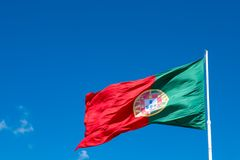 National flag of Portugal on a flagpole in front of blue sky. Stock Photo