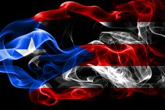 National flag of Puerto Rico made from colored smoke isolated on black background. Abstract silky wave background. stock photos