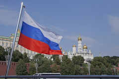 National flag of Russia against bridges of the Moskva River and the Kremlin. Royalty Free Stock Images