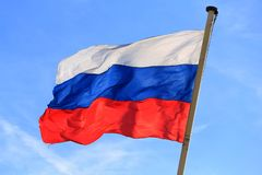 Flag of the Russian Federation. The national flag of the Russian Federation in the wind against a blue sky royalty free stock images