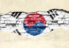 National flag of South Korea on a brick background. Brick wall with partially destroyed plaster, background or texture stock images
