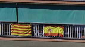 The national flag of Spain and the flag of Catalonia are hung out together on the balcony of the building in Catalonia Stock Photos