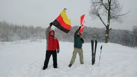 National flag of Switzerland and Germany waving in the wind. With blurred mountains in the background. Two people hold the flags in a blizzard and a strong wind stock footage